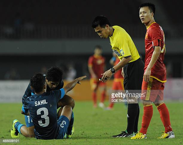 Singapore's Sahil talks to the referee after becoming injured during the VietnamSingapore football match at the 27th Southeast Asian Games in...