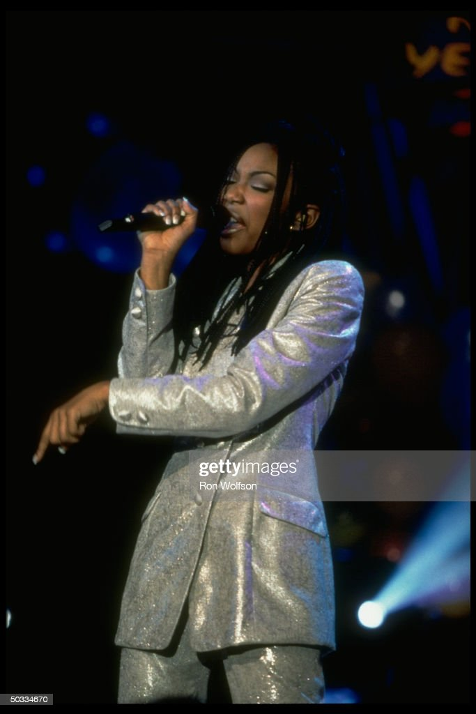 Singer Actress Brandy singing into microphone on stage during concert
