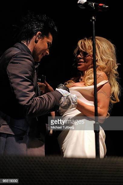 Singer Adam Lambert has a look at what's under actress Pamela Anderson's dress onstage at the 4th Annual Gridlock New Years Eve party held on the...