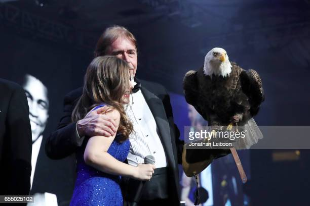 Singer Amelia DeMilo embraces American Eagle Foundation Founder and President Al Louis Cecere as he holds a bald eagle named Challenger onstage...