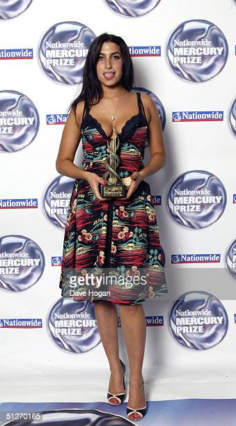 Singer Amy Winehouse poses in the pressroom at the annual 'Nationwide Mercury Music Prize' at the Grosvenor House on September 7 2004 in London The...