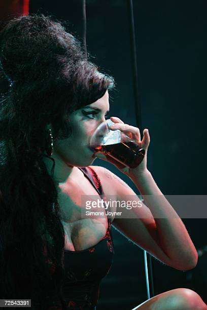 Singer Amy Winehouse takes a drink as she performs live on stage at Koko in Camden Town on November 14 2006 in London England