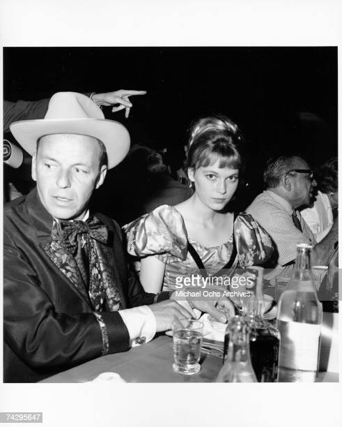 Singer and actor Frank Sinatra and actress Mia Farrow attend the SHARE Boomtown benefit party in 1965 in Los Angeles California