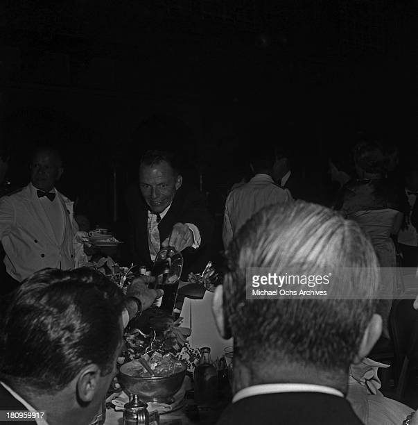 Singer and actor Frank Sinatra reaches for a bottle of Scotch at the premiere party for 'A Star is Born' on September 29 1954 in Los Angeles...
