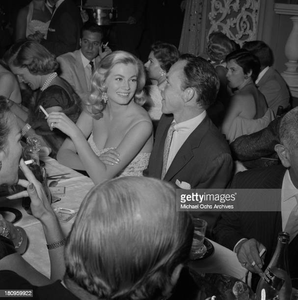 Singer and actor Frank Sinatra with actress Anita Ekberg at Romanoff's Restaurant on August 1 1955 in Los Angeles California