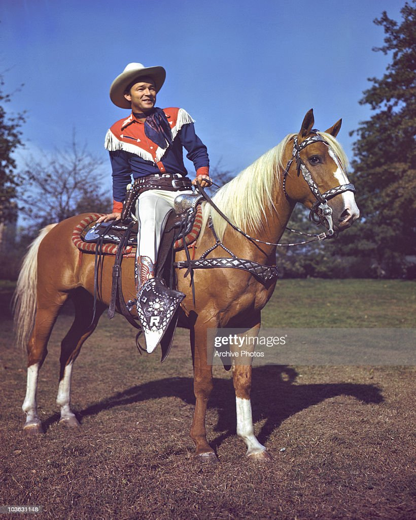 Singer and actor Roy Rogers pictured astride his palomino horse Trigger USA circa 1945 Rogers is wearing a costume of red white and blue