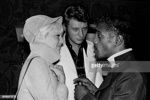 US singer and actor Sammy Davis Jr chats on June 20 1967 with French singers Sylvie Vartan and Johnny Hallyday backstage of the Olympia concert hall...