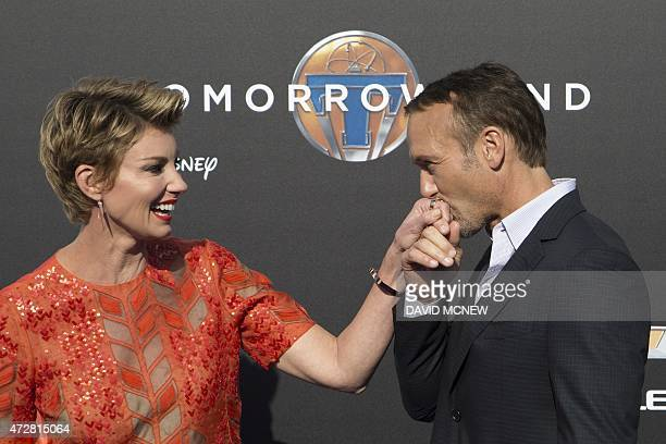 Singer and actor Tim McGraw kisses the hand of singer Faith Hill at the premiere of Disney's Tomorrowland in Anaheim California on May 9 2015 AFP...