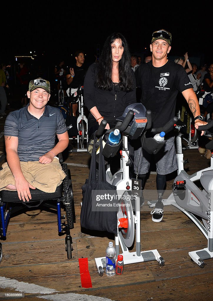 Singer and actress Cher (C) participates in the Cycle For Heroes: A Rock Inspired Ride On Santa Monica Pier with military veterans Isaac Blunt (L) and Brad Ivanchan (R) at Santa Monica Pier on September 11, 2013 in Santa Monica, California.