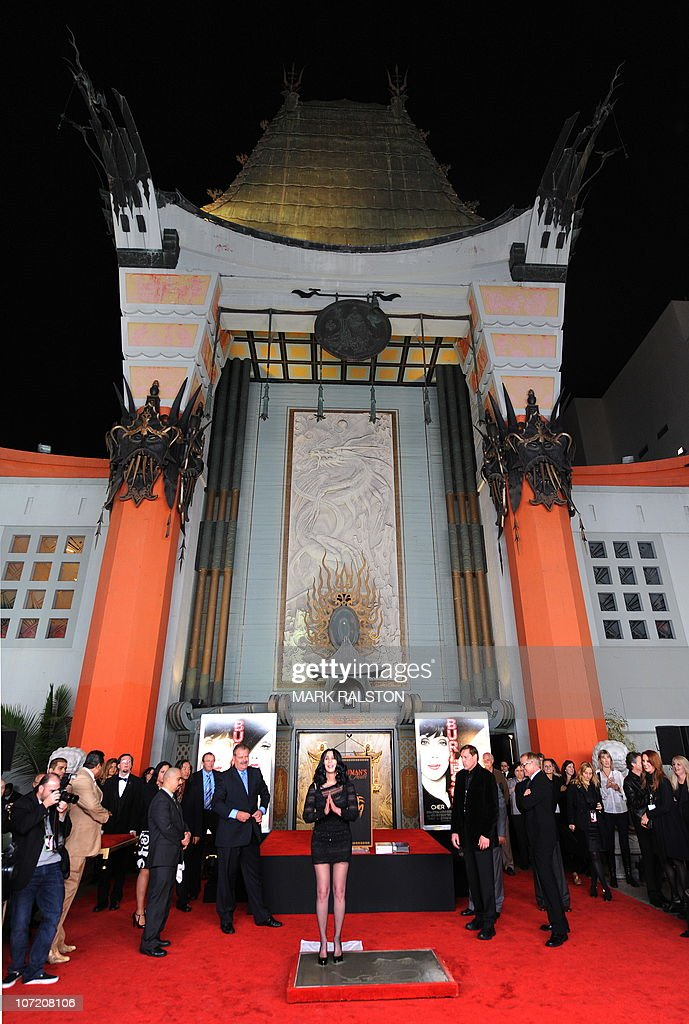 Singer and actress Cher stands in wet cement as she is immortalized at her hand and footprint ceremony outside the historic Grauman's Chinese Theatre...