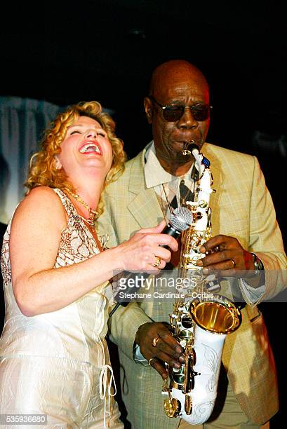 Singer and actress Jeane Manson laughs as saxophonist Manu Dibango plays his saxophone during the Bordeaux wine presentation at Pavillon Gabriel in...