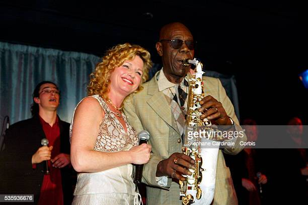 Singer and actress Jeane Manson smiles as saxophonist Manu Dibango plays his saxophone during a Bordeaux wine presentation at Pavillon Gabriel in...