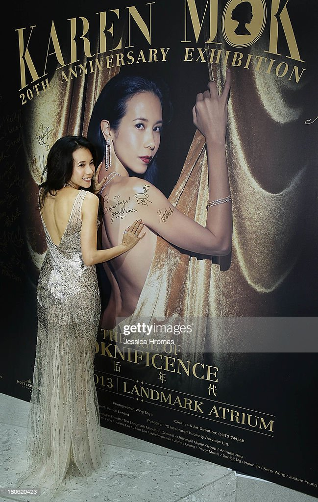 Singer and actress Karen Mok poses with a poster of herself at the opening of the Karen Mok 20th Anniversary Exhibition at the Landmark building, Central on September 15, 2013 in Hong Kong, Hong Kong.