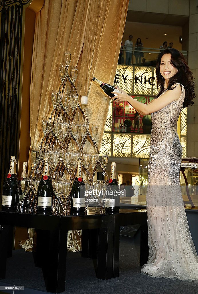Singer and actress Karen Mok pours champagne at the opening of the Karen Mok 20th Anniversary Exhibition at the Landmark building, Central on September 15, 2013 in Hong Kong, Hong Kong.