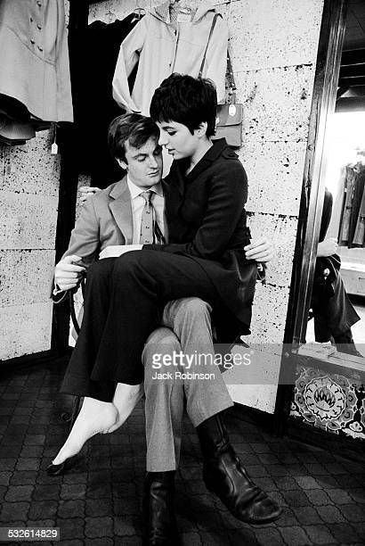 Singer and actress Liza Minnelli sits on the lap of singer Peter Allen late 1960s