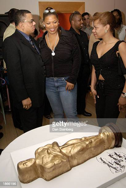 Singer and actress Queen Latifah talks with relatives in front of her Oscar statuette shaped birthday cake at her surprise birthday and preOscar...