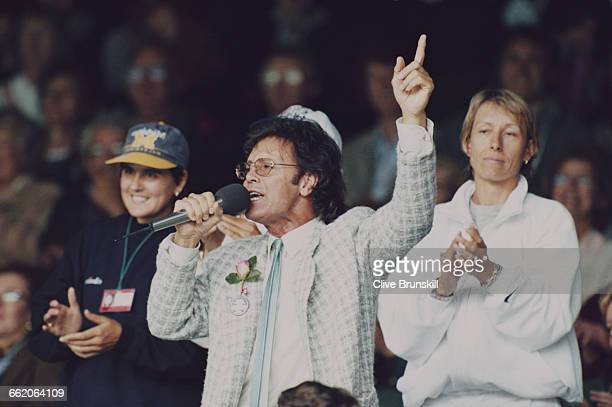 Singer and entertainer Sir Cliff Richard entertains the crowd alongside Martina Navratilova and Conchita Martinez by leading them in a song during a...