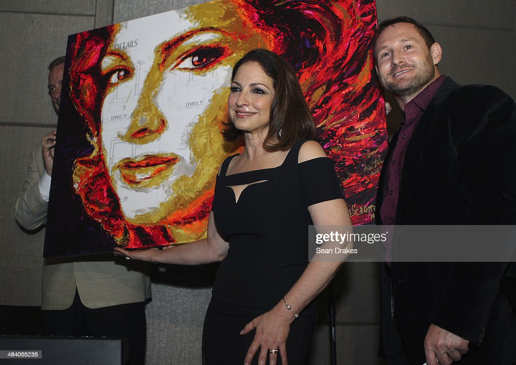 Singer and entrepreneur Gloria Estefan poses with a portrait of herself by artist Havi Schanz who sold the art piece for U$650000 at the VIP...