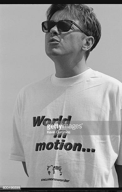 Singer and guitarist Bernard Sumner of English rock group New Order wearing a promotional tshirt after the group recorded the official song of the...