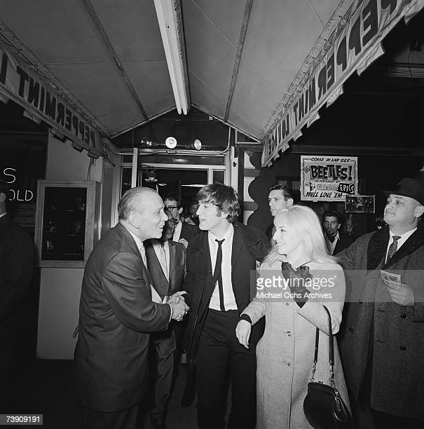 Singer and guitarist John Lennon of the rock and roll band 'The Beatles' and his wife Cynthia Lennon are greeted when they arrive at the Peppermint...