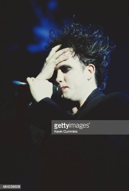Singer and guitarist Robert Smith performing with English pop group The Cure circa 1991