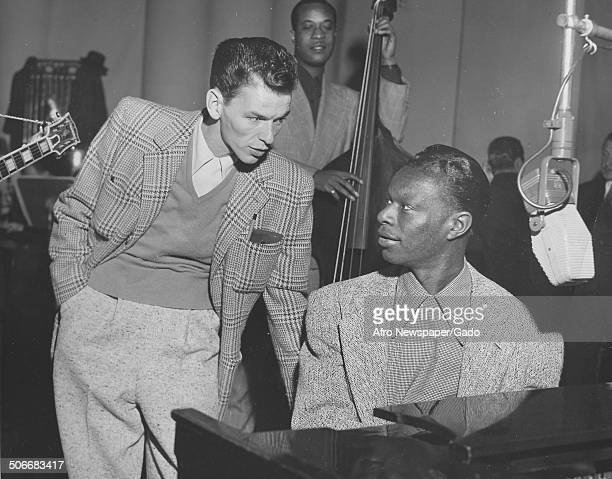 Singer and Jazz musician Nat King Cole and singer Frank Sinatra playing music during a radio show December 1945