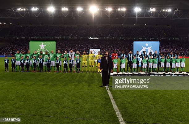 A singer and players stand in line while the French national anthem is played in tribute to victims of Paris' attacks prior to the French Ligue 1...