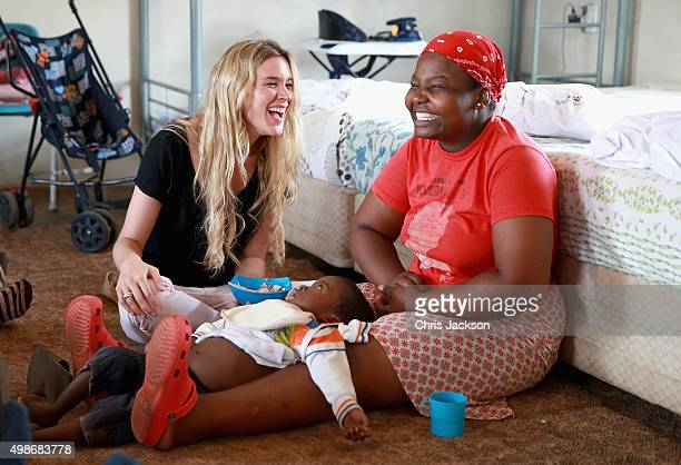 Singer and Sentebale Ambassador Joss Stone sings with a carer called Ntseliseng as she helps feed a young child called Monyake at Phelisanong...