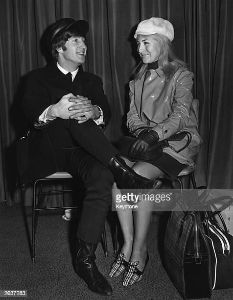 Singer and songwriter John Lennon of pop group The Beatles with his wife Cynthia wait for a flight to New York from London Airport John is wearing...