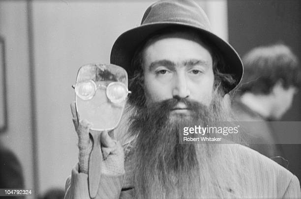 Singer and songwriter John Lennon of The Beatles in a false beard during filming of 'Help' directed by Richard Lester 1965 He is holding up a mirror...