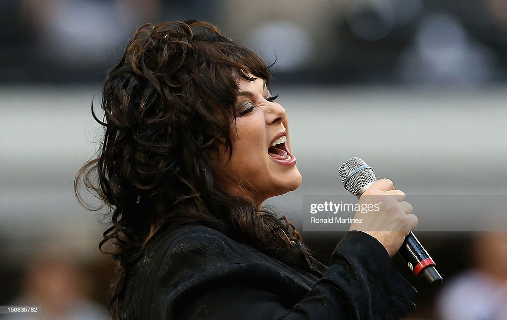 Singer Ann Wilson performs the national anthem before a Thanksgiving Day game between the Washington Redskins and the Dallas Cowboys at Cowboys Stadium on November 22, 2012 in Arlington, Texas.