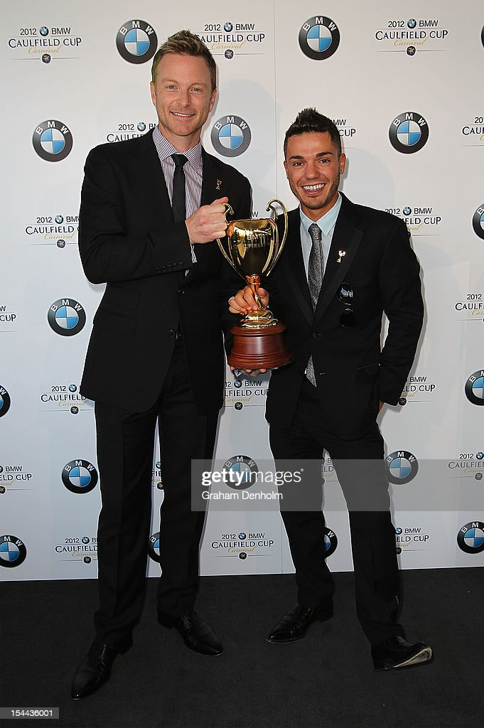 Singer Anthony Callea (R) and Tim Campbell hold the Caulfield Cup as they attend Caulfield Cup Day at Caulfield Racecourse on October 20, 2012 in Melbourne, Australia.