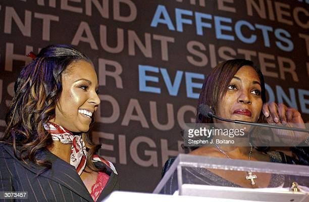 Singer Ashanti watches her mother Tina Douglas wipe tears from her eyes as they speak on stage at the Kennedy Center for the Performing Arts on March...