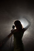 Singer backlit with arm raised