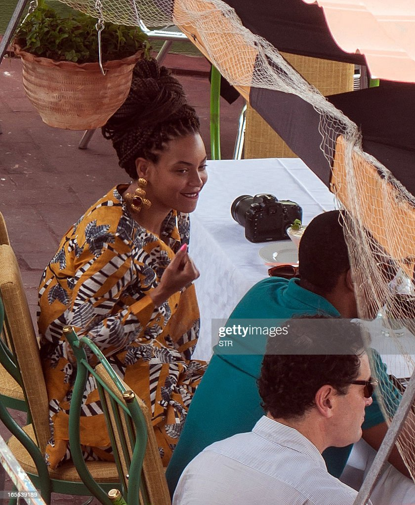 US singer Beyonce is seen in a private restaurant in Havana, next to her husband Jay Z (green shirt), on April 4, 2013.