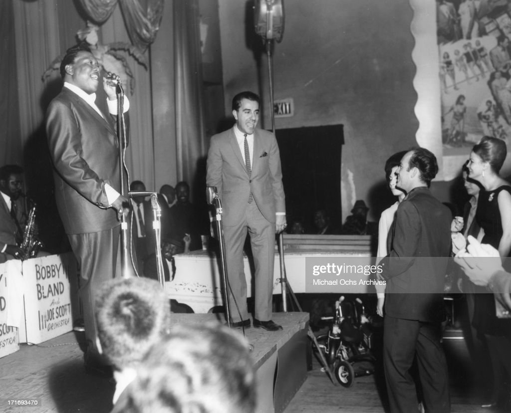 Singer Bobby 'Blue' Bland performs onstage with the Joe Scott Orchestra and club owner Jimmy Menutis as people dance in the audience in Houston Texas