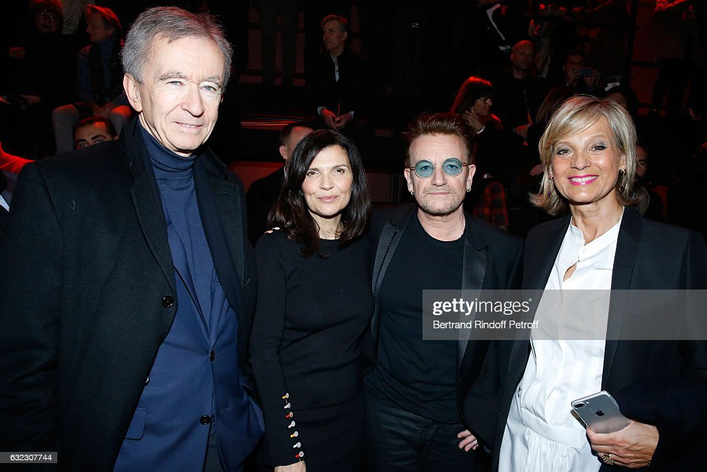 Singer Bono and his wife Ali Hewson standing between Owner of LVMH Luxury Group Bernard Arnault and his wife Helene Arnault attend the Dior Homme Menswear Fall/Winter 2017-2018 show as part of Paris Fashion Week on January 21, 2017 in Paris, France.