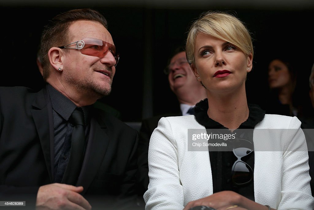 Singer <a gi-track='captionPersonalityLinkClicked' href=/galleries/search?phrase=Bono+-+Singer&family=editorial&specificpeople=167279 ng-click='$event.stopPropagation()'>Bono</a> and South African actor <a gi-track='captionPersonalityLinkClicked' href=/galleries/search?phrase=Charlize+Theron&family=editorial&specificpeople=171250 ng-click='$event.stopPropagation()'>Charlize Theron</a> arrive for the official memorial service for former South African President Nelson Mandela at FNB Stadium December 10, 2013 in Johannesburg, South Africa. Over 60 heads of state have travelled to South Africa to attend a week of events commemorating the life of former South African President Nelson Mandela. Mr Mandela passed away on the evening of December 5, 2013 at his home in Houghton at the age of 95. Mandela became South Africa's first black president in 1994 after spending 27 years in jail for his activism against apartheid in a racially-divided South Africa.