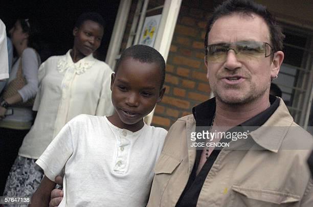 U2 singer Bono poses with a Rwandan boy with heart problems 18 May 2006 at a health center in Mayange Rwanda AFP PHOTO/JOSE CENDON