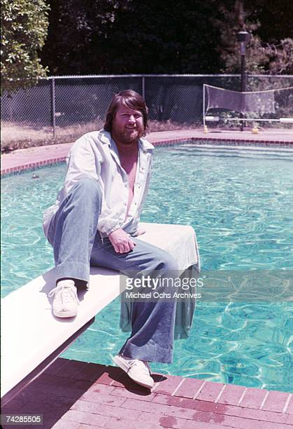 Singer Brian Wilson of the rock and roll band 'The Beach Boys' sits at a patio table in 1976 in Los Angeles California