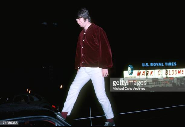 Singer Brian Wilson of the rock and roll band 'The Beach Boys' walks on top of a car across the street from Mark C Bloome Tire shop on Sunset...