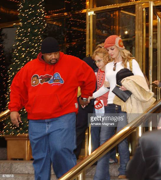 Singer Britney Spears holds hands with one of her bodyguards December 8 2001 as she exits the Trump International Hotel in New York with her younger...