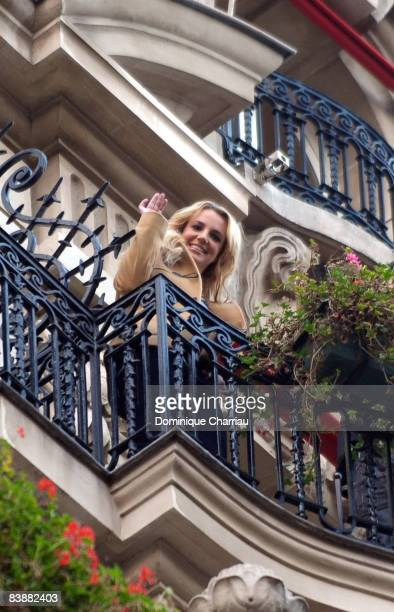 Singer Britney Spears waves to her fans from the balcony of the Plaza Athenee Hotel on November 28 2008 in Paris France