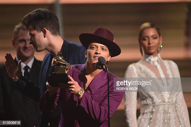 Singer Bruno Mars holds the award for the Record of the Year Uptown Funk as Mark Ronson and Beyonce look on onstage during the 58th Annual Grammy...