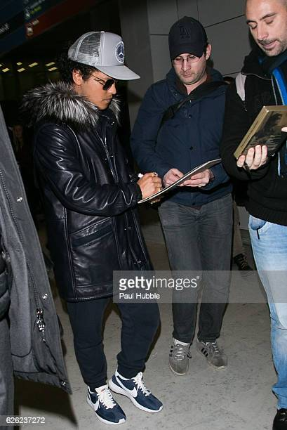 Singer Bruno Mars signs autographs as he arrives at Aeroport Roissy Charles de Gaulle on November 28 2016 in Paris France