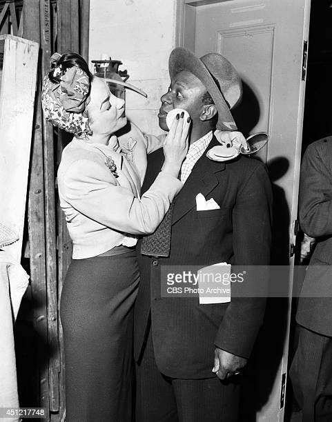 Singer Carmen Miranda applies makeup to surprised actor Eddie 'Rochester' Anderson during a break in rehearsals for the CBS radio program 'ELGIN...