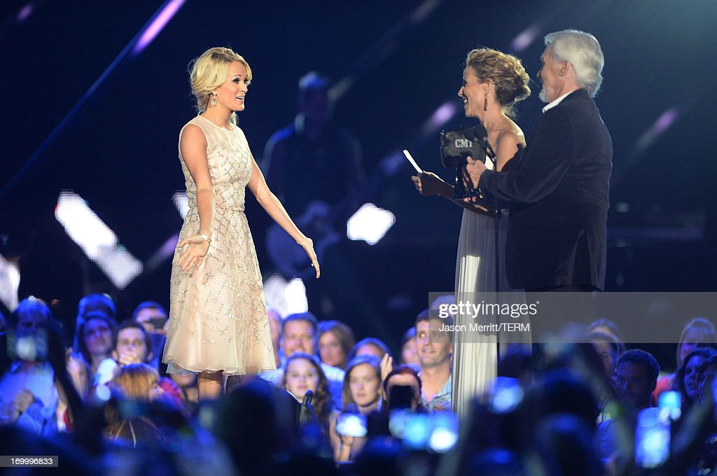 Singer Carrie Underwood accepts an award from Kenny Rogers and Sheryl Crow during the 2013 CMT Music awards at the Bridgestone Arena on June 5, 2013 in Nashville, Tennessee.
