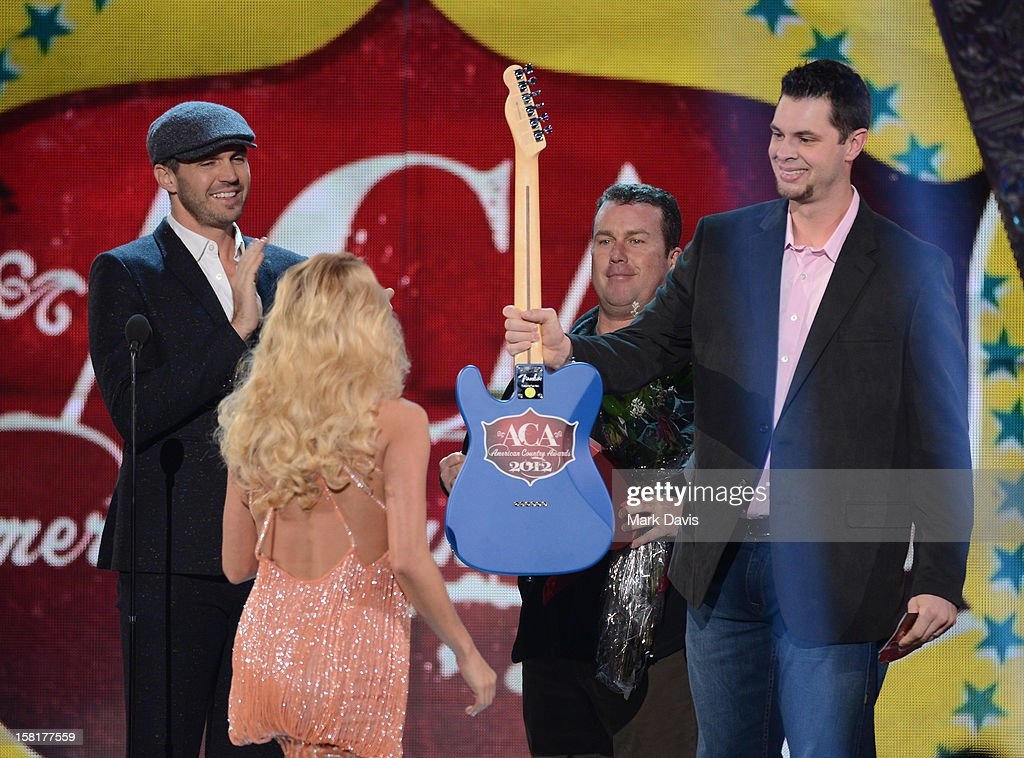 Singer Carrie Underwood (C) accepts the award for Artist of the Year from presenters Barry Zito (L), Rodney Carrington and Brandon Belt (R) onstage during the 2012 American Country Awards at the Mandalay Bay Events Center on December 10, 2012 in Las Vegas, Nevada.