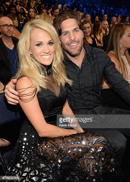 Singer Carrie Underwood and NHL player Mike Fisher attend the 2015 CMT Music awards at the Bridgestone Arena on June 10 2015 in Nashville Tennessee