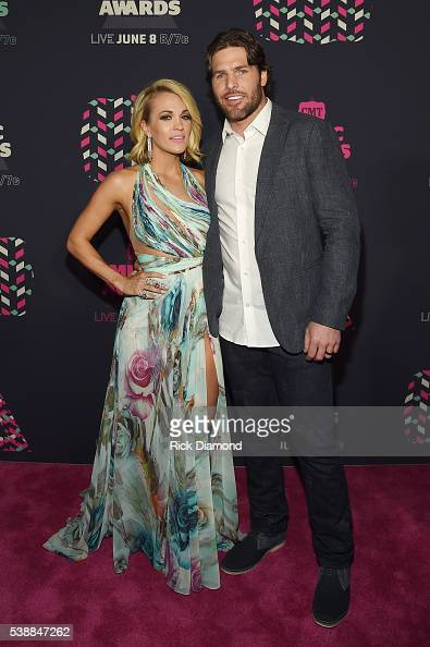 Singer Carrie Underwood and NHL player Mike Fisher attend the 2016 CMT Music awards at the Bridgestone Arena on June 8 2016 in Nashville Tennessee